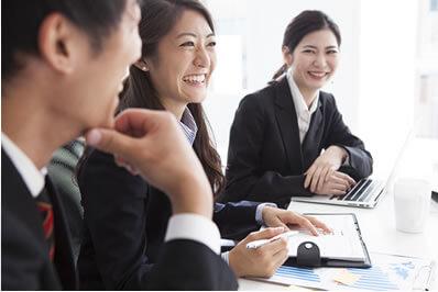 打ち合わせ中に笑顔を見せる女性社員のイメージ