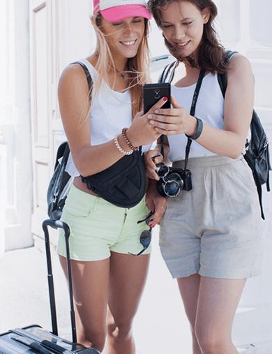 2人の女性観光客が一緒にモバイルバッテリーを使用しているイメージ