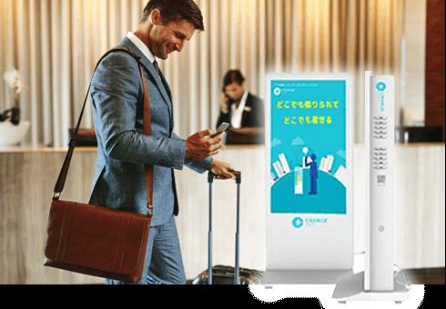【ホテルのフロントにモバイルバッテリースタンドを設置したイメージ】出張でホテルを利用するサラリーマンが、ホテルのフロントでスマートフォンを操作している様子の写真